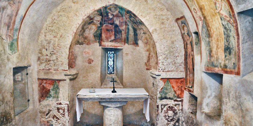 Apsis der Magdalenenkapelle. In der Nische links, ist das gemalte Tau, das Franziskus eigenhändig aufgetragen haben soll, zu sehen. Heute befindet es sich unter einer schützenden Glasplatte.