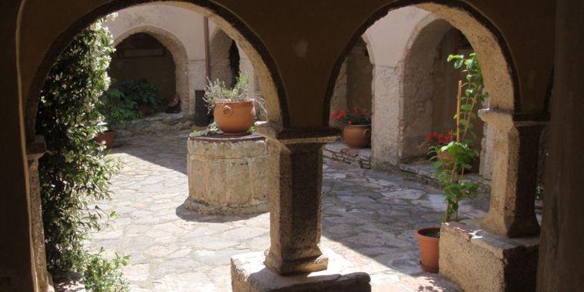 Blick in den Innenhof der Einsiedelei von Poggio Bustone. In der Mitte des kleinen Platzes ein gemauerter Brunnen. Wasser, als Symbol des Lebens, erinnert auch an den Sonnengesang des heiligen Spielmanns.