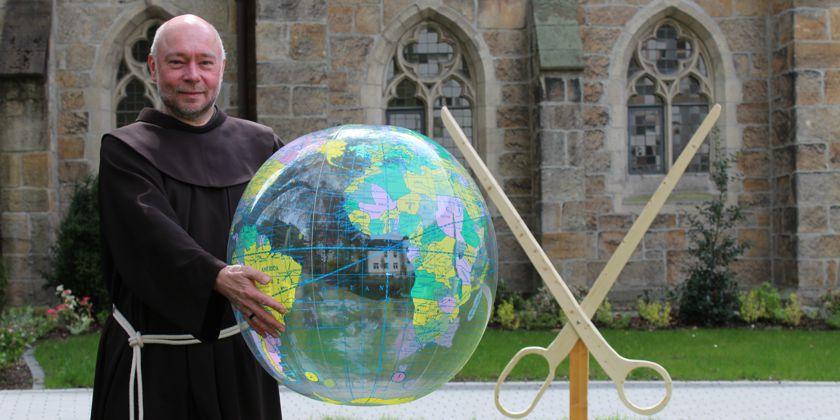 Bruder Augustinus hält den Globus im Arm. Die Franziskaner Mission setzt sich mit ihrem Engangement weltweit für die Ärmsten der Armen ein.