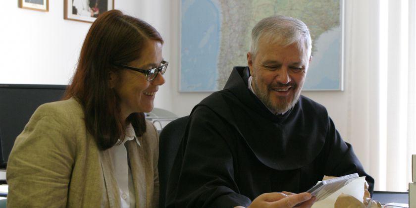 Bruder Alfons, der Leiter der Franziskaner Mission München mit seiner Mitarbeiterin Pia Wohlgemuth bei einer Projektbesprechung.