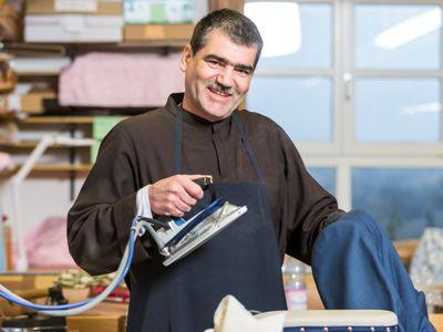 Bruder Gerhard bereitet in seiner Schneiderei den Zuschnitt für ein neues Ordensgewand (Habit).