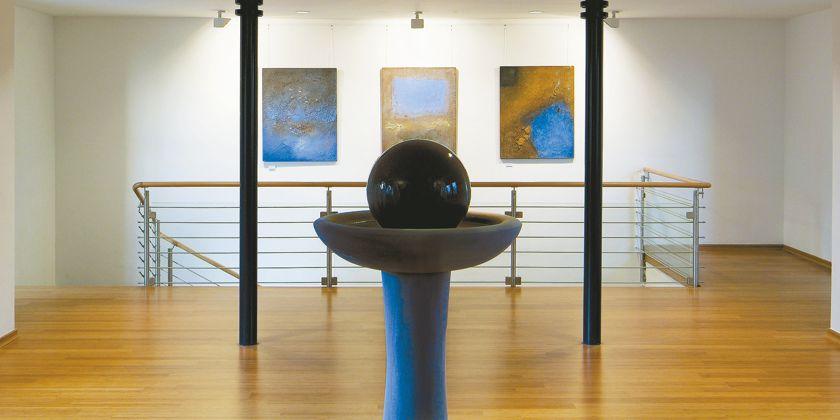 Brunnensteele mit einer blauen Keramikkugel vor dem Eingang zur Meditationskapelle.