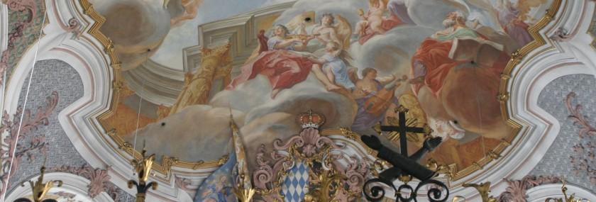 Detail des Freskos in der im Rockokko-Stil wieder errichteten Kirchenapsis. Auf dem Broncegitter ist das franziskanische Wappen mit den über Kreuz liegenden Armen angebracht.