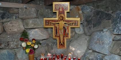 Die kleine Kapelle aus Bruchsteinen lädt zum stillen Verweilen ein. Auf dem Steinsimms brennen Lichter vor einem Damianokreuz.