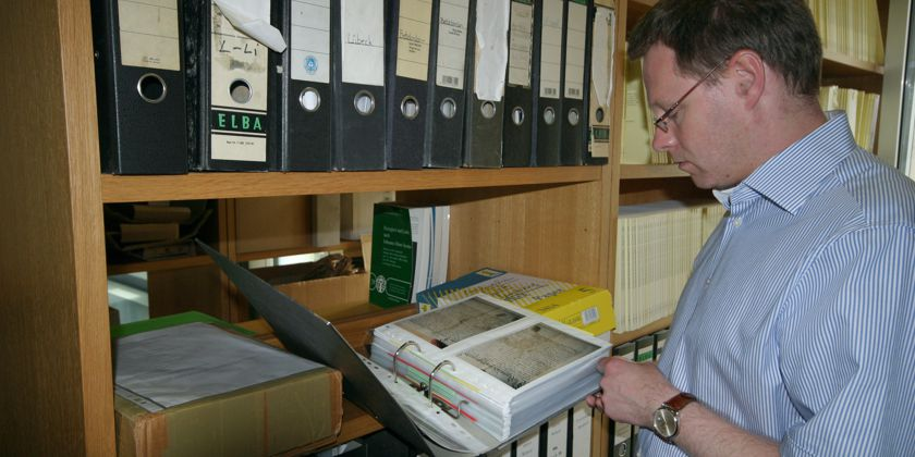 Forschungsteamleiter Bernd Schmies begutachtet alte Akten im Archiv in Münster