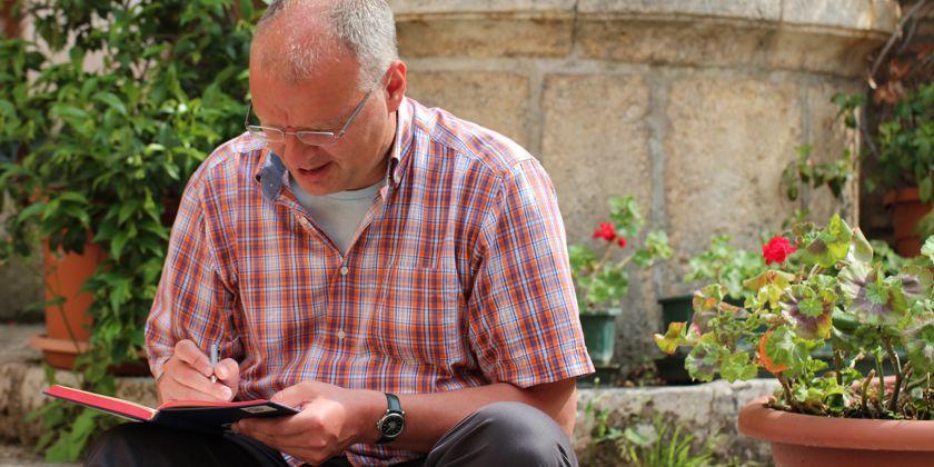 Bruder Frank schreibt im Garten Ideen für einen geistlichen Impuls in sein Notizbuch