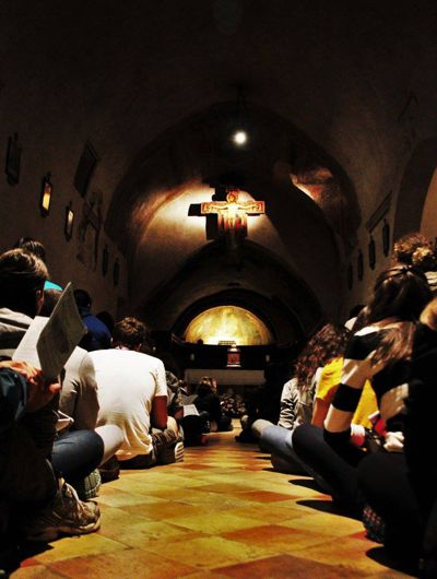 Junge Menschen beten vor der Kreuzikone von San Damiano. Bild von Servizio Otientamento Giovani (Assisi 2016)