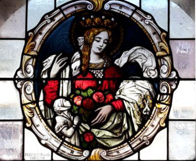 Buntglasfenster mit der Darstellung der heiligen Elisabeth in der Pfarrkirche in Dollberg. Zu den Attributen dieser heiligen Frau gehören besonders der Korb mit Rosen und Brot. Zur linken kniet eine kleine Frau, es ist die Stifterin des Bildes. Bild von Bruder Gabriel Gnägy.