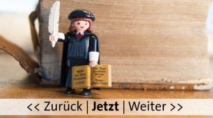 Playmobil Figur von Martin Luther vor einem alten Buch. Bild von Helmut Blum, pixelio.de